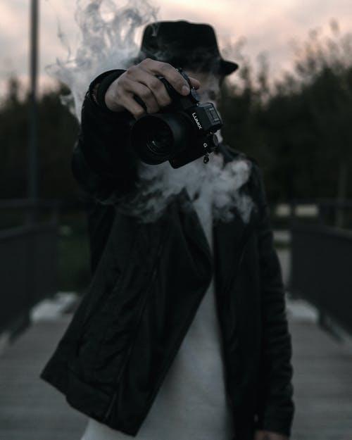 Person holding Panasonic Lumix GH5S camera smoking