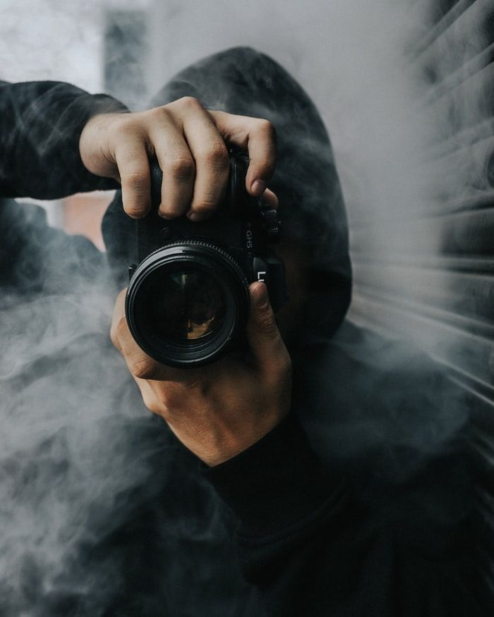 Photographer holding Panasonic Lumix GH5S camera in smoke