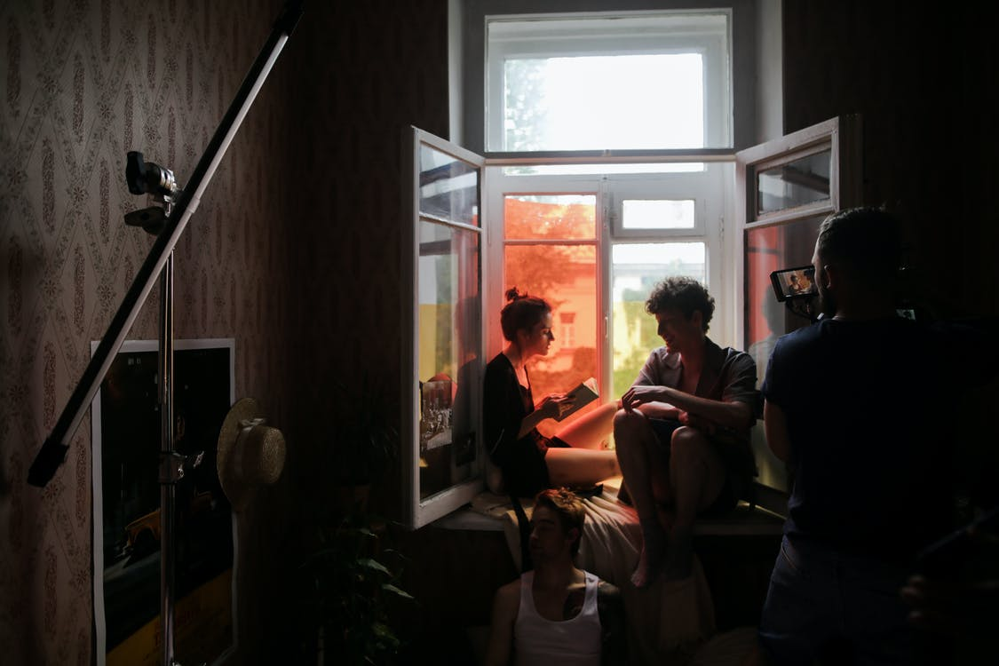 Filmmaker shooting a documentary about young couple in a dark room sitting by a window