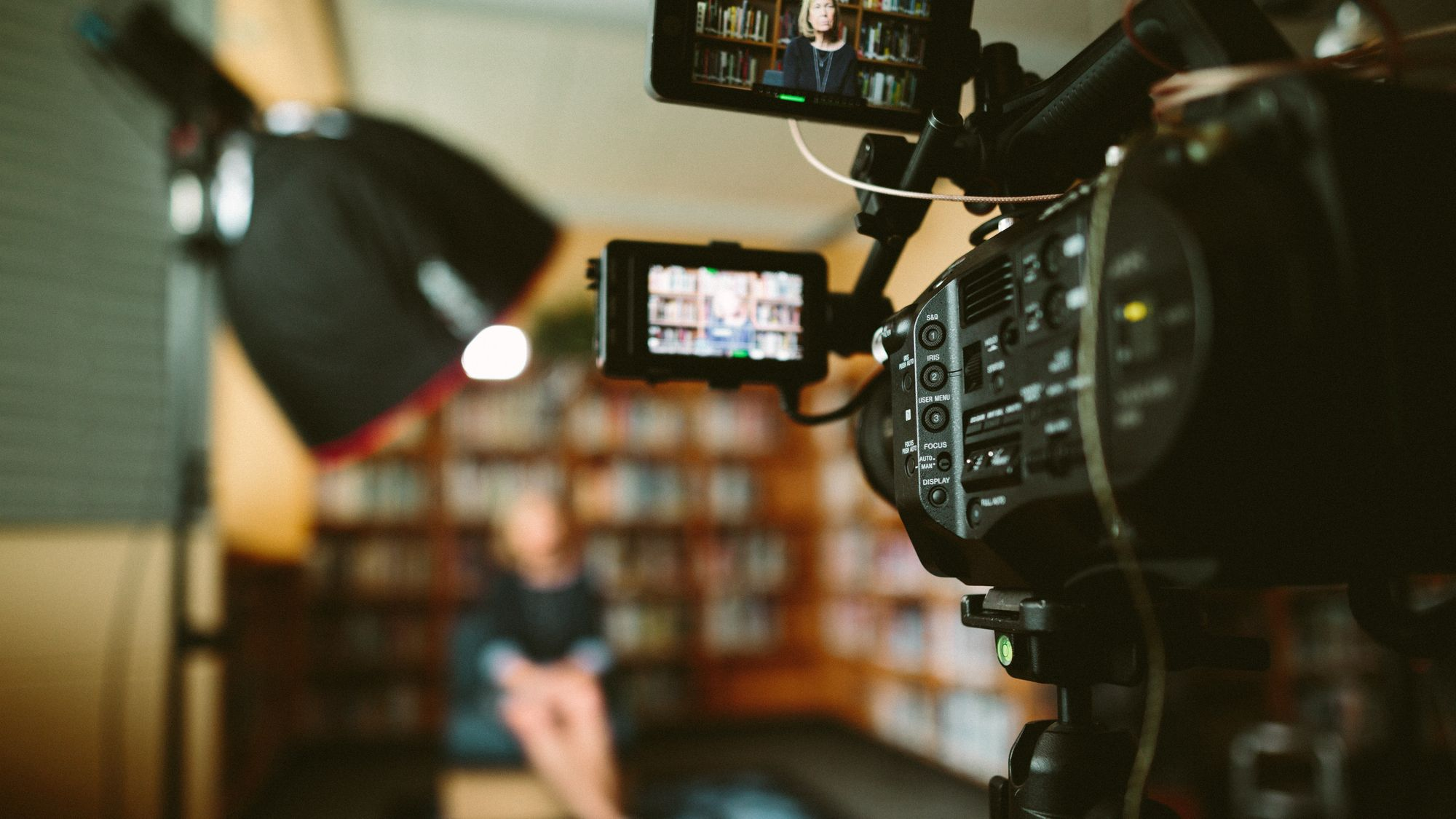 videographer-recording-woman-in-front-of-bookshelves