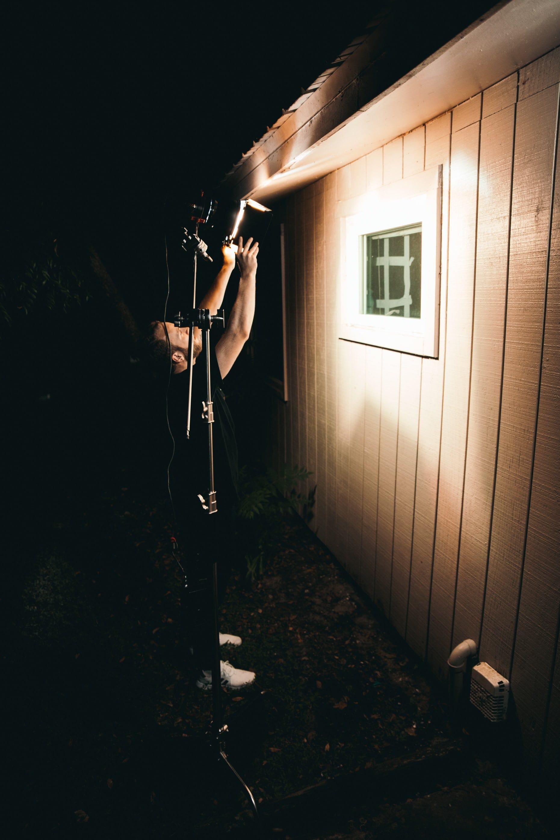 man-lighting-a-window-from-outside