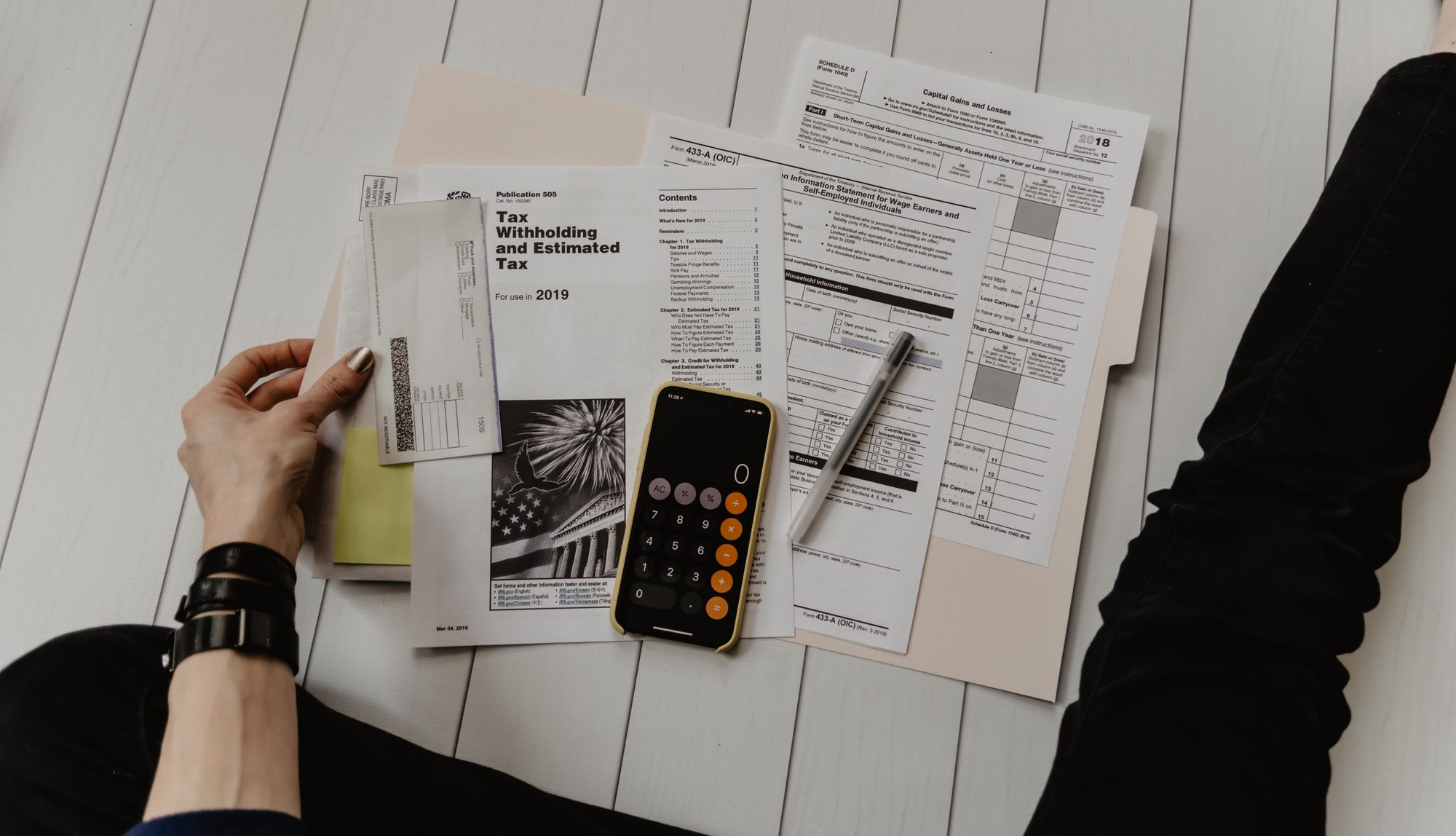 person-holding-financial-papers-and-calculator