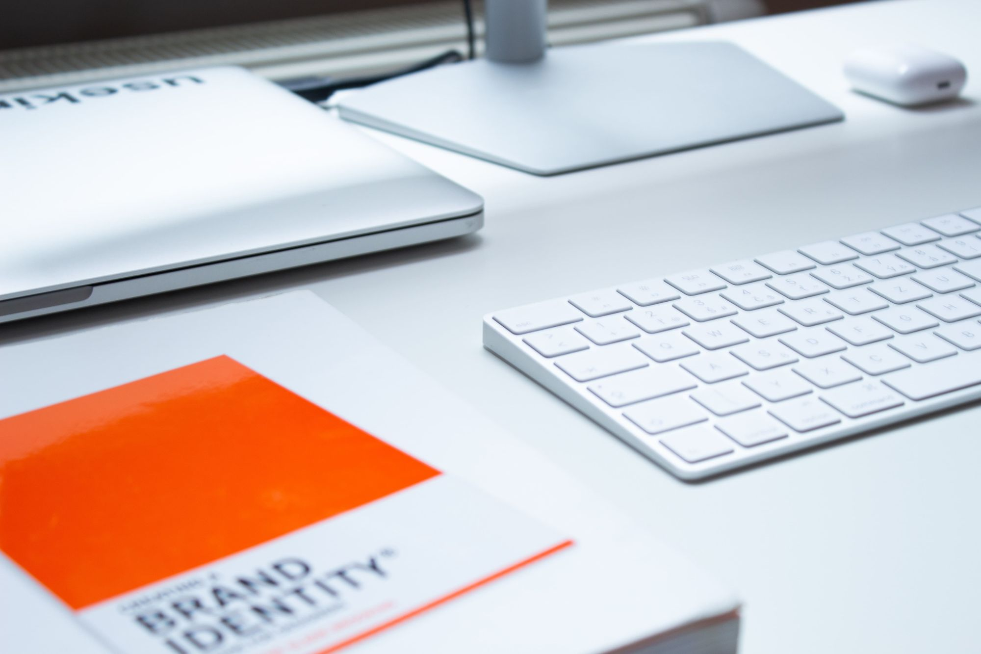 book-on-brand-identity-with-macbook-on-table