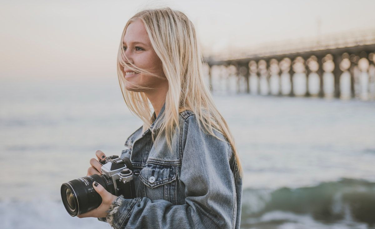 photographer standing on a seaside by a bridge